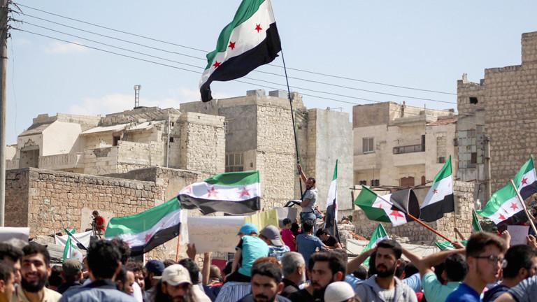 Menschen schwenken Fahnen der Opposition in Idlib.