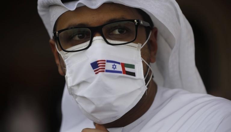 Mann mit einem Mundschutz, auf dem die Flagge der USA, Israels und der Vereinigten Arabischen Emirate abgebildet ist.