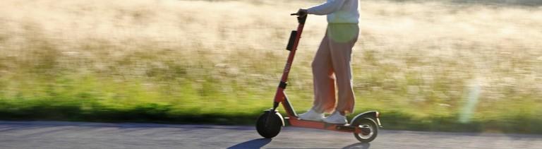 Frau auf einem E-Scooter, die an einem Kornfeld vorbeifährt.