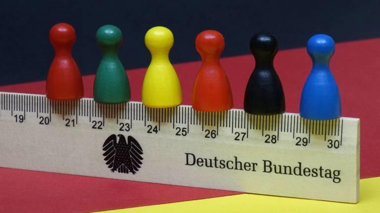 Verschiedenfarbige Spielfiguren, die für die jeweiligen Farben der populärsten Parteien in Deutschland stehen