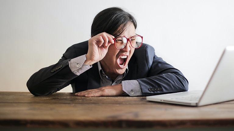 Ein Mann vor einem Laptop verzieht das Gesicht