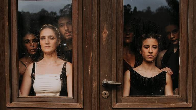 Junge Menschen stehen hinter einer verschlossenen Glastür