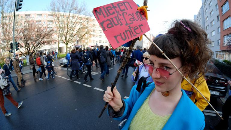 """Frau bei einer Demo mit dem Schild """"Mieten rauf, Laune runter""""."""