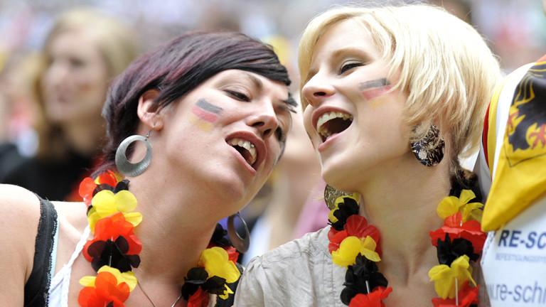 Zwei Fans der deutschen Fußball-Nationalmannschaft singen die deutsche Nationalhymne.