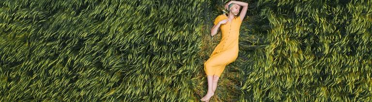 Frau liegend auf Wiese/Feld
