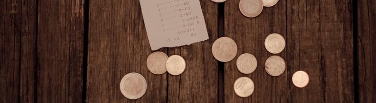 Geld und ein Kassenbon liegen auf einem Holztisch