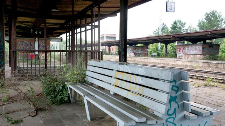 Stillgelegter Bahnhof mit leerer Bank