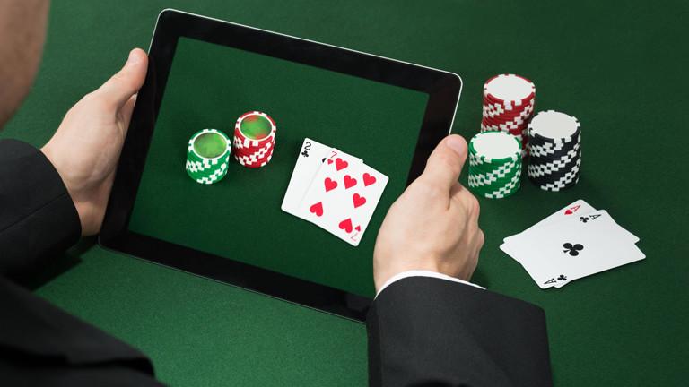 Symbolfoto: Spiele-Chips und Poker-Karten auf einem Tablet.