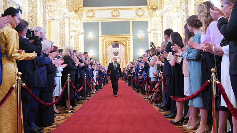 Mann schreitet über einen roten Teppich, Gäste applaudieren.