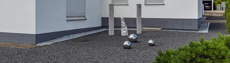Schottergarten vor einem Einfamilienhaus.