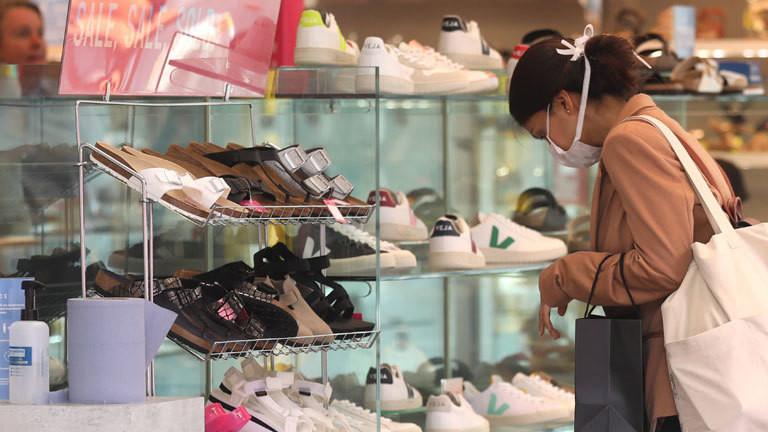 Frau mit Mundschutz vor einem Schuhregal