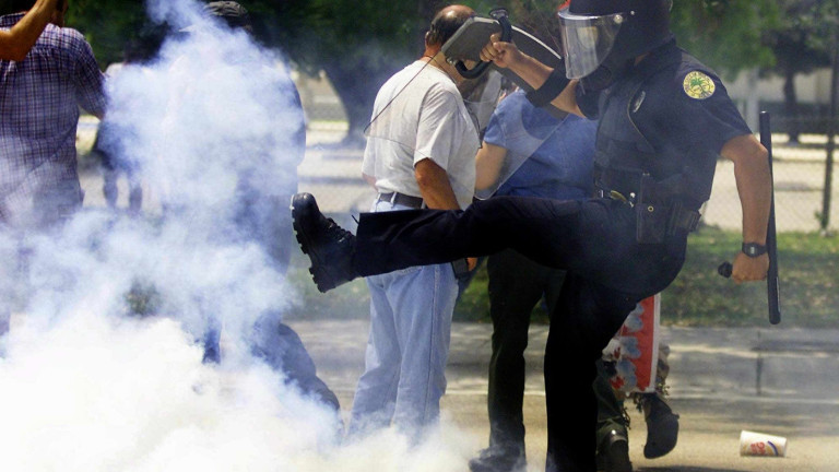 A Miami police officer kicks a tear gas canister as they try and brake up a concentration of protestors in a street of the Little Havana district in Miami