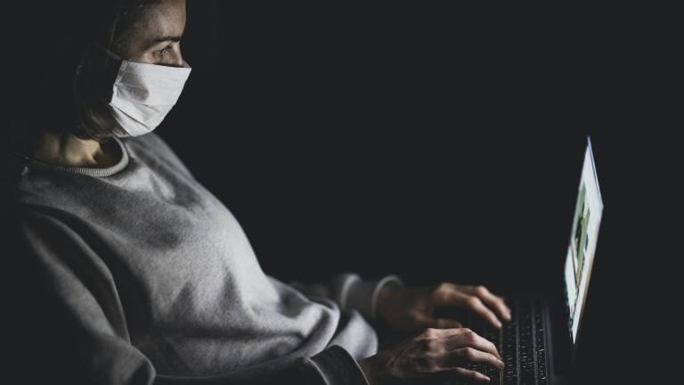 Frau mit Mundschutz und einem Laptop auf den Knien.