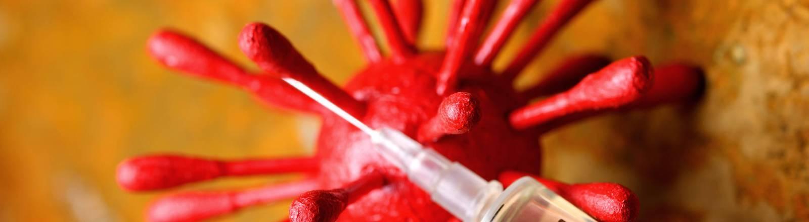 Symbolfoto: Impfspritze liegt auf Coronavirus-Modell