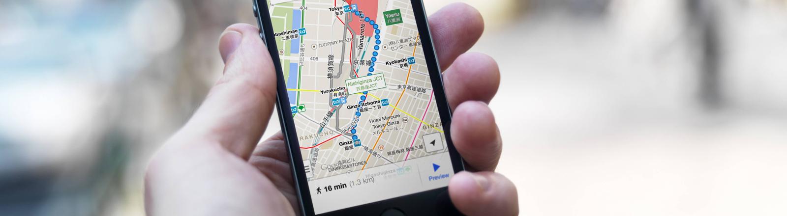 Eine Hand hält ein iPhone mit Google Maps auf dem Display