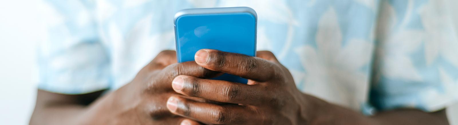 Mann hält Smartphone in der Hand