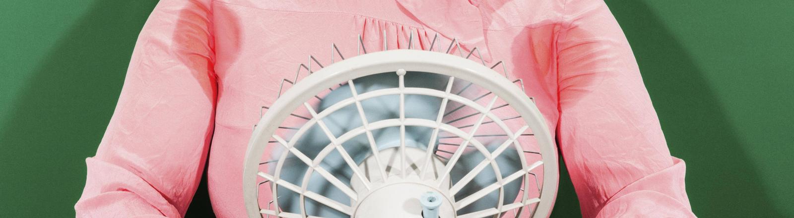 Schwitzende Frau mit Ventilator