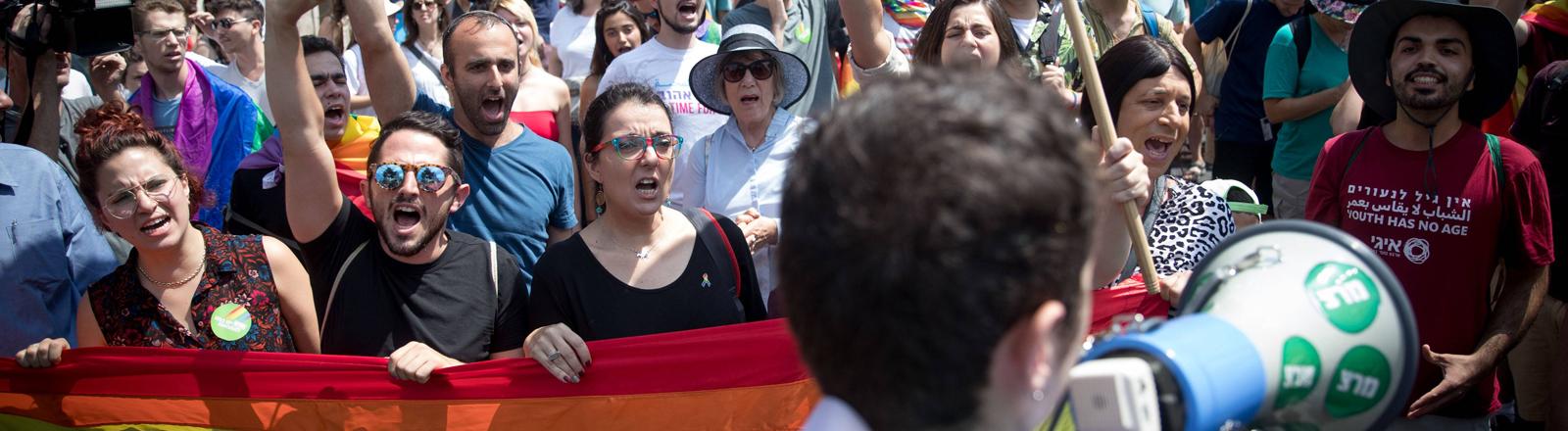 Menschen mit Regenbogenfahne demonstrieren.