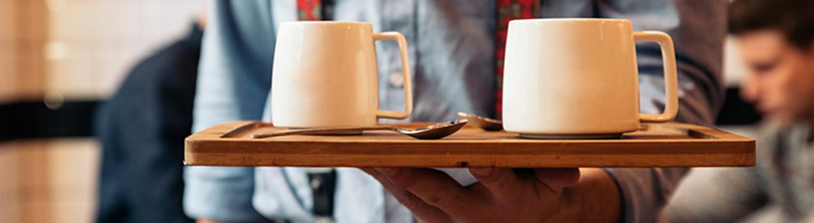 Mann hält Tablett mit Kaffeetassen in den Händen