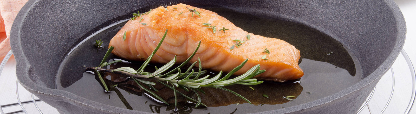 Grilled Salmon Fillet With Thyme, Rosemary And Olive Oil In A Cast Iron Pan
