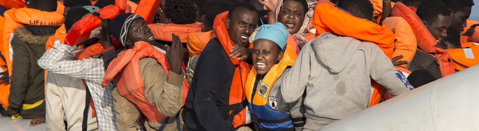 Menschen in einem sehr vollen Schlauchboot.