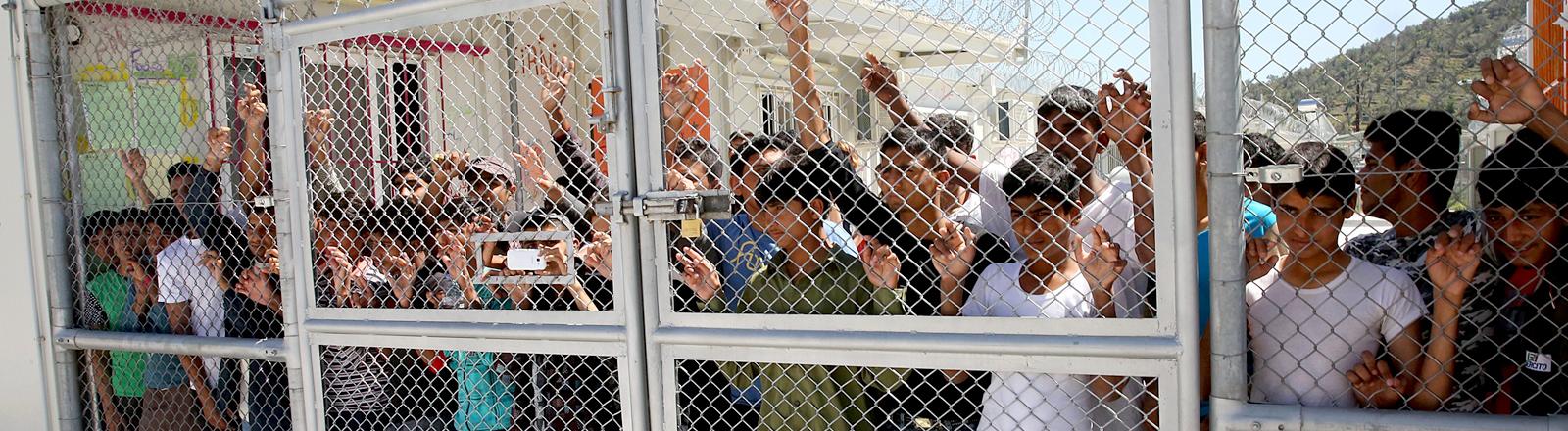 Menschen hinter einem Zaun.