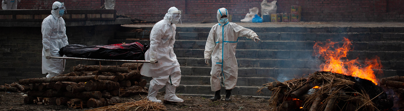 Coronavirus Emergency In Nepal Workers donned in Personal Protective Equipment (PPE) carry a body of a deceased who succumbed to COVID-19 for cremation on the bank of Bagmati River in Kathmandu, Nepal on Tuesday, May 4, 2021.