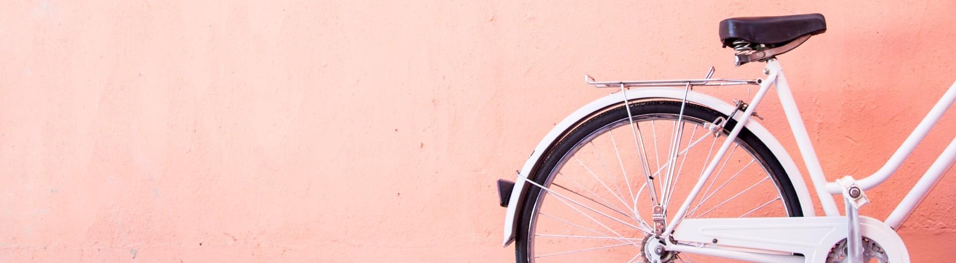 Weißes Fahrrad vor einer orangen Wand