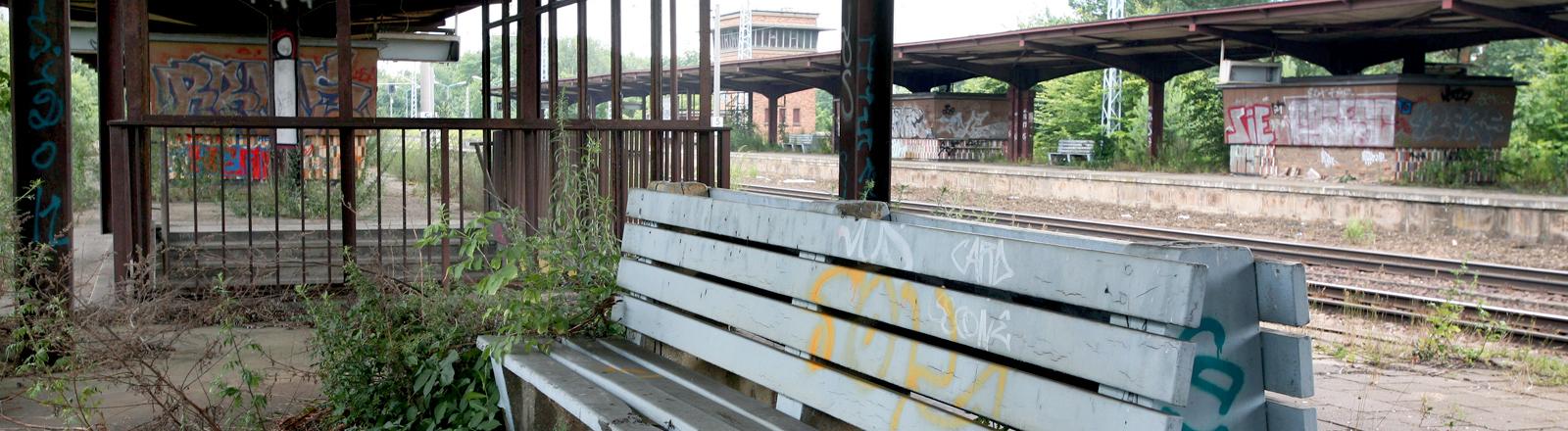 Stillgelegter Bahnhof mit leerer Bank.