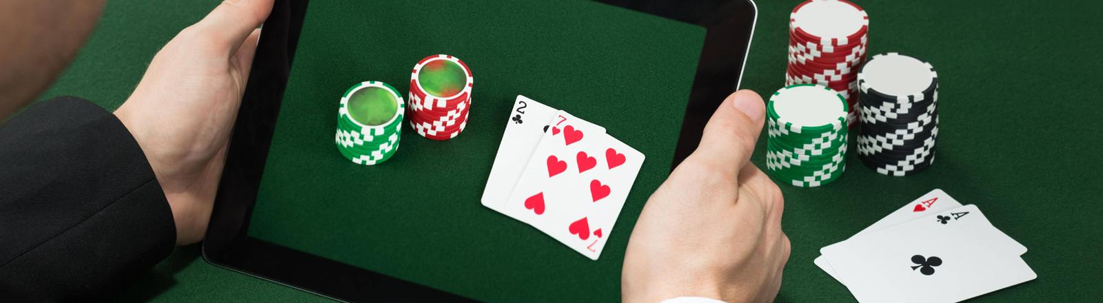 Symbolfoto: Spiele-Chips und Poker-Karten auf einem Laptop.