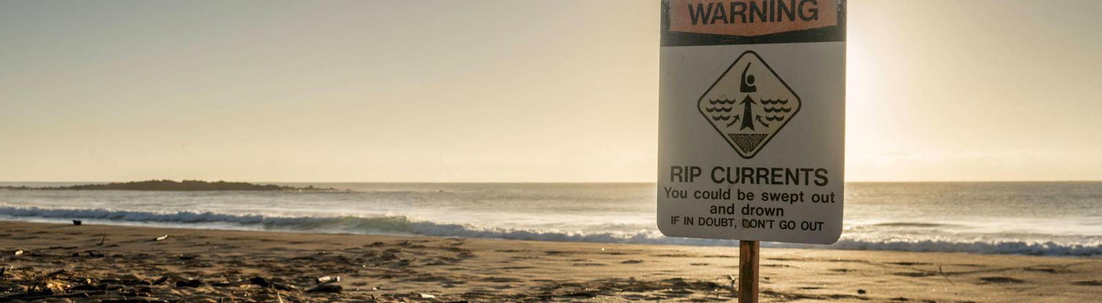 Schild am Strand warnt vor gefährlicher Strömung
