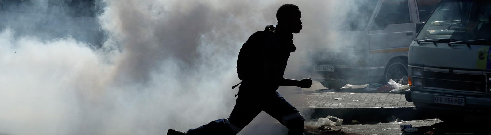 03.09.2019, Südafrika, Johannesburg: Ein Mann rennt vor Tränengas davon, nachdem er sich mit Waren aus einem Geschäft in Germiston östlich von Johannesburg eingedeckt hatte. Die Polizei hatte zuvor bei Unruhen Gummigeschosse auf die Plünderer abgefeuert.