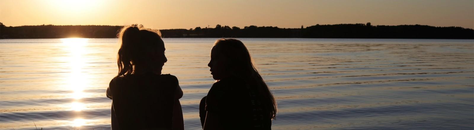 Zwei junge Frauen sitzen im Sonnenuntergang am Strand und unterhalten sich.