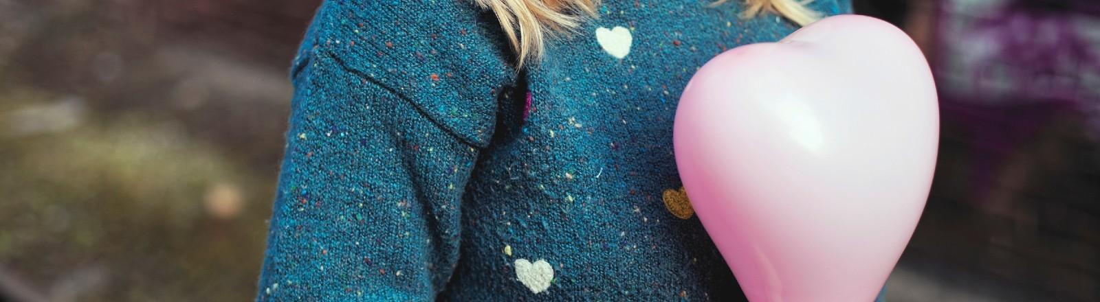 Junge Frau trägt einen Pulli mit bunten Herzen und hält einen Luftballon in Herzform in der Hand.
