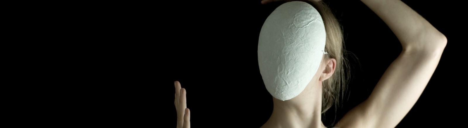 Eine Frau versteckt ihr Gesicht hinter einer Maske.