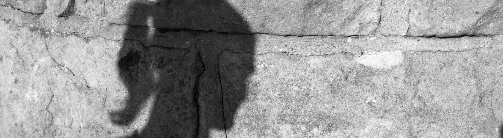 Der Schatten einer Frau an einer Mauer.