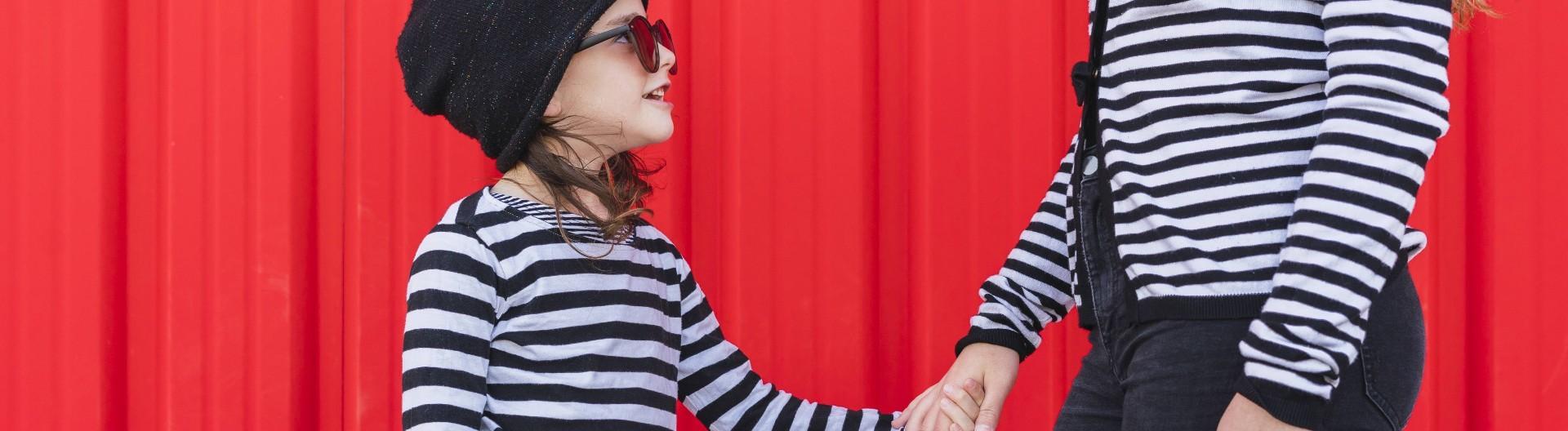 Kleines Mädchen hält die Hand seiner Mutter. Beide tragen Partnerinnenlook.