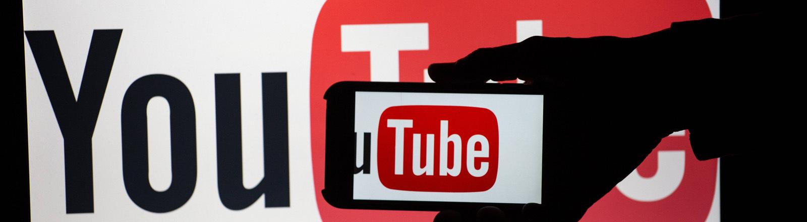 Logo von Youtube auf Flatscreen mit Hand davor, aufgenommen auf Messe in München, 23.8.2018