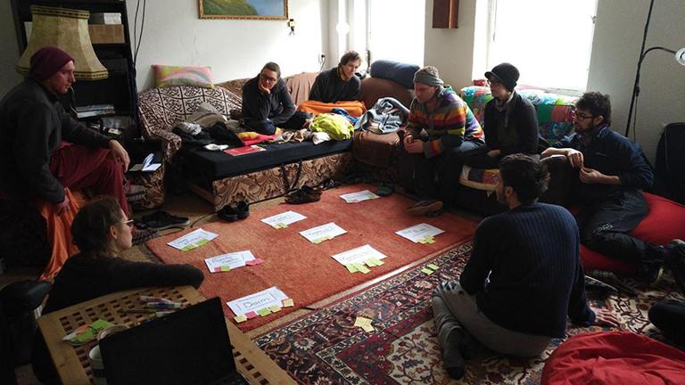 Mehrere Menschen sitzen im Kreis auf dem Boden und einem Sofa.