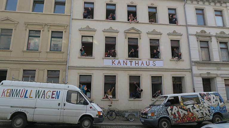 Aus jedem Fenster eines Hauses winken Menschen, auf einem Schild steht Kanthaus.