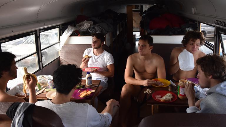 Junge Männer frühstücken gemeinsam in einem umgebauten Schulbus