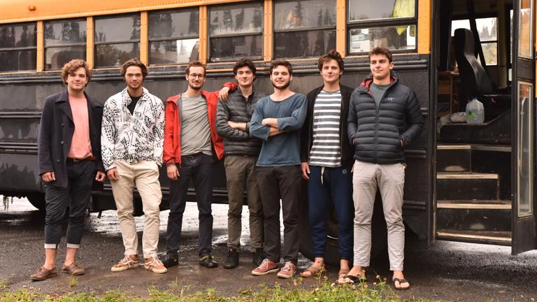 Gruppenbild sieben junger Männer vor ihrem zum Reisebus ausgebauten Schulbus