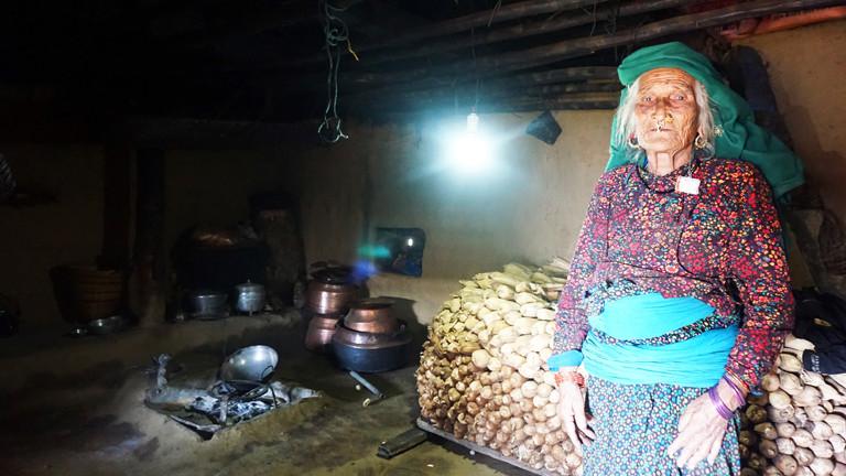 Zum ersten Mal im Leben elektrisches Licht : eine Dorfbewohnerin in ihrer Lehmhütte - Nepal