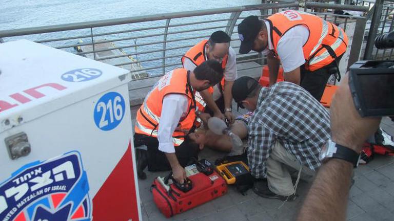 Vier Männer beugen sich über einen Jungen, der auf dem Boden liegt.