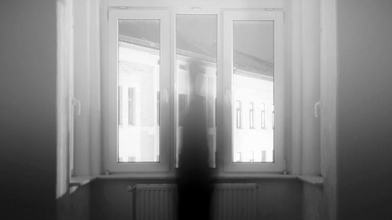 Eine schemenhafte Figur ist an einem Fenster zu erkennen.