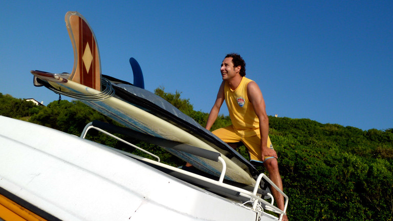 Christian Rex steht vor Surfbrettern auf dem Dach seines VW-Bullis.