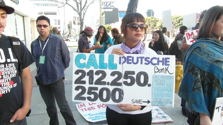 Eine Frau hält ein Protestplakat gegen die Deutsche Bank hoch.