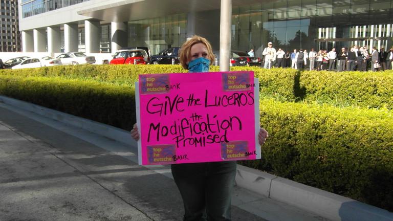 Eine Frau hält ein Protestplakat hoch. Sie protestiert für die Familie Lucero.
