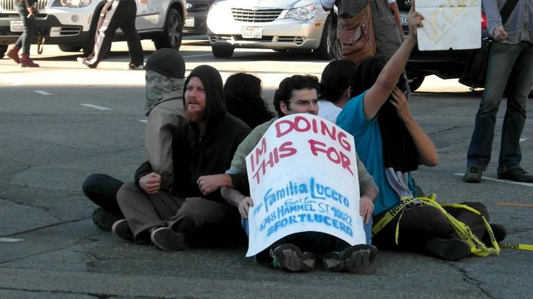 Männer sitzen auf dem Boden mit einem Plakat, mit dem sie für die Familie Lucero protestieren.