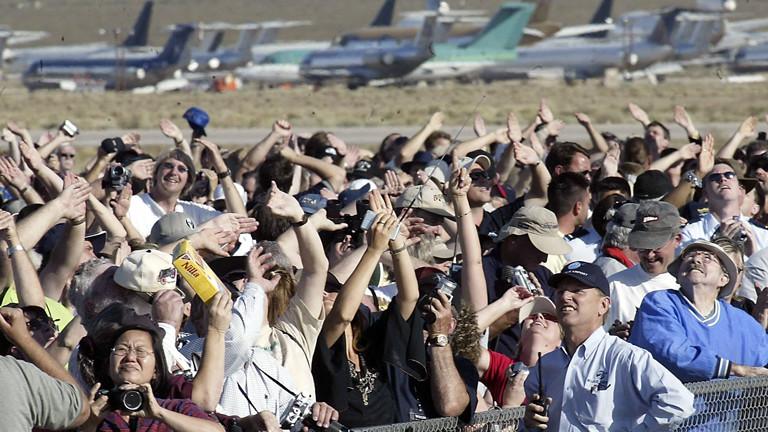 Zuschauer, die in den Himmel schauen und Fotos machen.